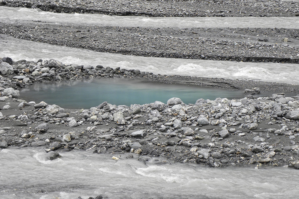 Water running from Fox Glacier, across the glacier moraine, to the sea. This image was created in 2010 in the valley on New Zealand...